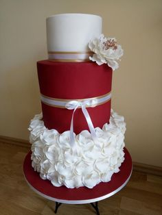 red and white wedding cake with ruffles and ribbon