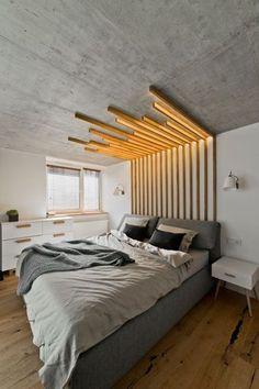 Cette tête de lit avec éclairage intégré a été conçue par l'architecte d'intérieur lituanienne Indre Sunklodiene, mais elle est facile à reproduire dans votre chambre grise ! Vissez des tasseaux en bois au mur de la tête de lit, et prolongez-les au plafond. Pour un effet graphique, coupez-les à des longueurs différentes. Pour intégrer l'éclairage, on fixe des bandes de LED le long des tasseaux : voilà un ciel de lit qui se transforme en plafonnier original !