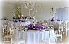 Monte Vista Venue purple table setup with a white tablecloth, silver under plates, white vase with a white tree inside with beads hanging from it, white tiffany chairs, centerpice surrounded purple net and a table name
