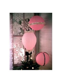 Paper lanterns decorated to look like oversized Christmas ornaments.