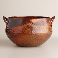 Our exclusive Hammered Copper Ice Bucket is an elegant entertaining essential with a two-sided design and a shimmering hammered finish. Featuring convenient carrying handles, this sleek ice bucket keeps drinks appropriately chilled and is easy to transport from the home bar to the entertaining area.