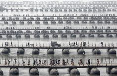 Pilgrims and devotees cross pontoon bridges at the Maha Kumbh Mela - the largest spiritual gathering on the planet, held every 12 years in India. (© Wolfgang Weinhardt)
