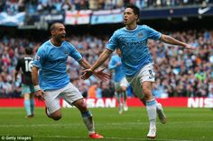Flying high: Nasri celebrates his opener with Zabaleta as the home fans go wild at the Etihad #PremierLeague2013/14