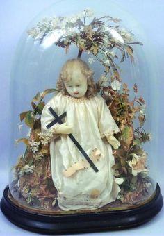 Grand Enfant Jésus en cire assis avec une croix sur ses genoux, présenté sous globe. Format: 60x40x28 cm. (XIXème)