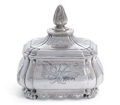 A DUTCH SILVER TOBACCO-BOX AND COVER  MARK OF JAN DIEDERIK PONT, AMSTERDAM, 1756  Oblong and on scroll and foliage feet, with shaped skirt, the sides and detachable cover each engraved with foliage and rocaille and rising to flammiform finial, engraved underneath with initials, marked underneath  5½ in. (14.2 cm.) high  18 oz. (572 gr.)