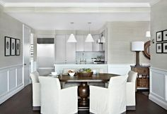 Chic dining room boasts upper walls clad in pale taupe grasscloth and lower walls clad in wainscoting surrounding an oval pedestal dining table lined with white slipcovered dining chairs accented with gray trim. Pedestal Dining Table, Round Dining Table, Dining Area, Dining Chair Slipcovers, Dining Room Furniture, Dining Chairs, Dining Rooms, Rattan Chairs, Room Chairs