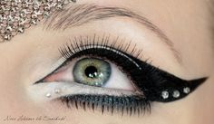 Winged cat eyeliner with gems in the corners. Whiter eyeliner on lower lid and fake bottom eyelash.   Defined eye. Big eye cosmetic application