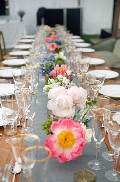 Low arrangements in pinks, white, blue and purple add a soft touch to the rustic tables.