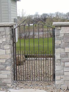 Iron gate with scroll top installed between stone columns