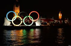 Illuminated Olympic rings are displayed near the Houses of Parliament with Big Ben in the background