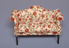 Queen Anne curved back settee upholstered in a floral print, with a one-piece seat cushion and hand-carved legs