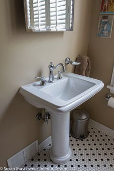 This small hall bath required a little facelift to make it both comfortable and updated. A new pedestal sink, with a to-scale, arced fixture, all anchored by a classic, black and white tiled floor, did just that.