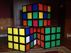 80s party Decor. Easy to make Rubiks cubes.  Use a square box, colored construction or scrapbook paper cut into squares to fit the box size, and black duct tape.  These are 2' on each side.