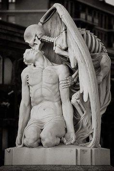 """Situada en el cementerio de Barcelona, esta brillante escultura llamada """"El beso de la muerte"""" representa en forma de esqueleto con alas a la muerte, la cual besa el cuerpo de un joven en la frente. Según la historia, en 1930, la familia Llaudet, estaba de luto por la muerte de su hijo y creó esta escultura para su tumba."""