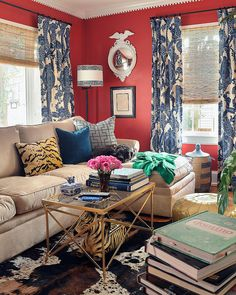 Colorful, eclectic living room with red walls, blue patterned drapes, neutral couch and natural woven shades
