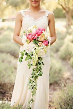 Beautiful cascade bouquet of peonies, tulips, hyacinth, blushing bride, and trailing foliage.