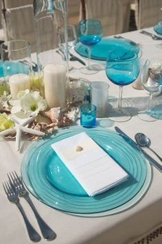 Sand-colored tablecloth, starfish  seashells in the decor, and blue seaglass-inspired glassware.