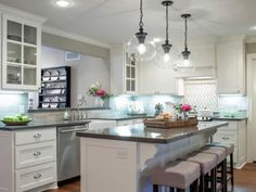 Now that's more like it — new appliances, industrial pendants and updated cabinets give a distinctive look to this space. A brand-new island and bartop, plus a stunning marble tile backsplash, add a hint of color.