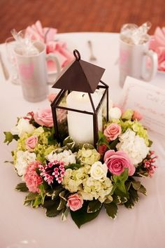 Make a wreath with shower colors/flowers, and then lay flat on table and place lantern in the middle of it.