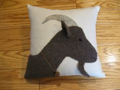 This is another goat pillow that Ive designed and is a profile of a brown Billy goat. Ive used plush felt and wool felt and stitched it neatly into place onto a prairie cloth fabric. This fellow has grey horns, a bead eye and a rusty bell around his neck. His ear is three dimensional. This pillow measures 11 x 11 and is firmly stuffed with polyester fibrefill. Comes from a pet and smoke free home. Many of my pillows are unique, one of a kind creations. I love to sew and come up with new…