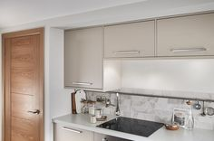 Cashmere is a soft and natural colour that can add a subtle hint of warmth to your kitchen.  Take a look at Howdens.