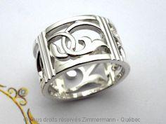 Un anneau ajouré en argent de 12 mm de large, quatre fenêtres avec motifs différents, fait entièrement à la main sans aucun moulage. Zimmermann Québec