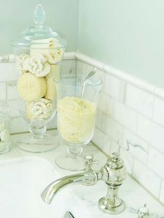 idea from Better Homes and Gardens - Simple Indulgence - A vintage silver soup ladle serves bath salts right out of a glass decanter and into the tub. Shapely glass jars -- a mix of family heirlooms and new vessels from discount stores -- show off salts, sponges, and cotton balls.