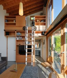 A rolling ladder made from salvaged wood and components leads to a small, yet well equipped, office. | Dwell Magazine