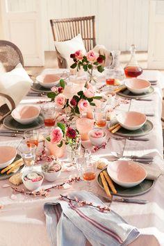 Mesa de comedor vestida con vajilla rosa y gris y muchas flores_ 00428792