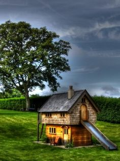 Garden with a tree (Walnut cottage two storey custom built wooden play house playhouse with shingle roof)