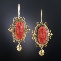 Measuring 1 1/2 inches long and lovely (they drop a bit further from the ear wires), these classic Victorian ear baubles, circa 1875, present a pair of classic beauties hand carved in high relief in rich salmon-colored corals. The cameos are magnificently framed in tri-color  (yellow, rose & white) 14K gold and support a dancing dangle. Consummate Victoriana.