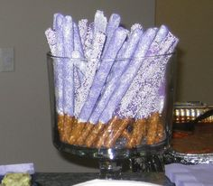 purple themed bridal shower treats - pretzel rods dipped in white candy melts and decorated with purple sprinkles and purple dipped candy melts with white sprinkles