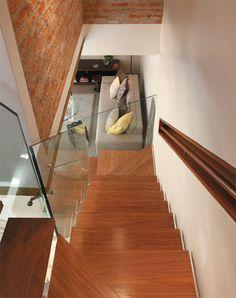 Na escada, há um tubo metálico central com pisadas de chapas metálicas. Essas peças serviram para a fixação dos degraus de cumaru e da barra metálica que prendeu o guarda-corpo de vidro (Penha Vidros). Embutido na parede, o corrimão é de cumaru. modo slideshow