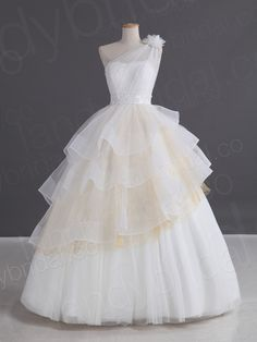 One-shoulder-strap ball gown wedding dress with tiered ruffles and one layer of golden hue in the middle.