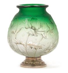 An etched glass vase on silver foot by Daum,