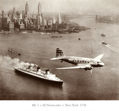 """A """"DC-3"""" flies over the """"ss Normandie"""", with Lower Manhattan, New York in the background."""