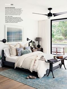 Athena and Victor Calderone's Hamptons summer house in Amagansett NY.  The master bedroom is a mixture of high and low.  The silk rug is from ABC Carpet, the bed is from Ikea...simply painted graphite grey, and the round side table is from CB2.  Love the Madeline Weinrib Blue Luce ikat pillows. The railroad bench and amish drawers are from Factory 20...my favorite online industrial antique & oddity shop! via Living Etc