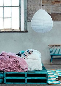 Coat refurbished pallets in Teal Bayou BEHR paint to get an eclectic and industrial feel in your bedroom. Pair this blue color with gold yellow tones in a geometric rug and painted vintage chair to bring the look together.