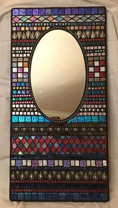 Espejo mosaico colorido con azulejos de vidrio con detalles en plata Espejo de sí mismo es oval, marco es rectangular Total: 12 pulgadas x 24 amplia pulgadas de longitud Espejo: 7 pulgadas de ancho x 11 3/4 de longitud Creado sobre un substrato de madera sellado Colgar el aparato