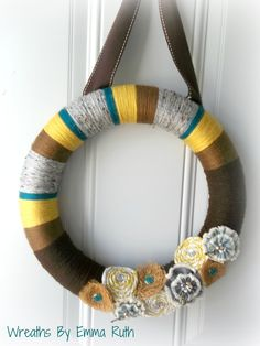 Rustic Fall Modern Yarn Wreath in Brown, Mustard Yellow, Teal and Gray with flower embellishments. via Etsy.