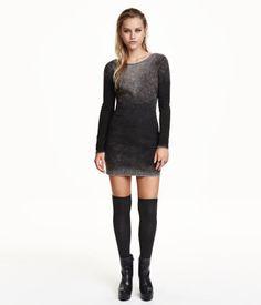 En kort, figurnära klänning i ribbad trikå. Klänningen har djupt ringad rygg och lång ärm.