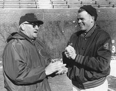 Chicago Bears head coach George Halas and quarterback Bill Wade rub their hands in order to keep warm during practice at Wrigley Field in 1962.