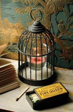 "Caged Candlelight    A captive flicker from a tea light or votive candle is suspended from miniature canary cages. 7""."