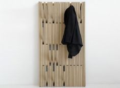 """The Piano hanger takes the traditional coat hanger and smushes it flat against the wall. Inspired by traditonal piano hinges, each hook swings out when needed, and then folds back flat after usage. The Piano is available in a large (32"""" x 58"""") and small size (15"""" x 58""""), and in two finishes; Beech Lacquer and Oak Varnish. Designed by Patrick Seha for Feld."""