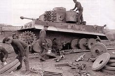 Major repairs being made to the roadwheels and suspension on this Tiger 1 tank in rough terrain.