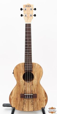 The unique spalted patterns in this figured maple uke makes this a beautiful, one of a kind instrument. The sound is  bright and clear with warm lower tones.  A real treat to play!  Spalted Maple (laminated) top, back and sides with Mahogany binding on top, back and sides. Rosewood fingerboard and bridge, Spalted Maple headstock overlay, nickel-silver frets. Black synthetic bone nut and saddle, mahogany neck, Grover open geared tuners, Aquila Nylgut strings and satin finish. Kala EQ with…