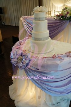 #Lavender #purple make a #great #match with #white. Having white #table #skirt around #cake #table with #spot #light and #purple #drapery with #bow and #crystal #buckle make the #wedding very #tren...