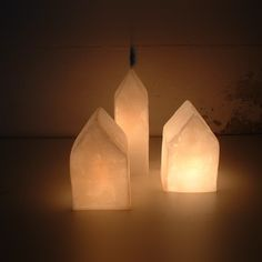 Lampade a forma di casette di un bianco candido che sembra di cera. Crea una luce calda, accogliente e intima. Racchiudono un mondo di storie, quelle degli immaginari abitanti che occupano le sue quattro mura. Un complemento d'arredo essenziale, nato dalla riflessione sulle forme della città. Materiale: Resina, pigmenti e luce, le trovi su http://lovli.it/index.php/casine-cascina.html#