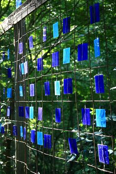 Stained glass & wire screen. Wire wrapped around the chunks of glass holds it in the center of the wire mesh. Use wire mesh fencing or concrete reinforcing mesh.