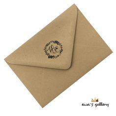 <h2>Kraftová obálka z recyklovaného papiera na svadobné oznámenie s kvetinovým venčekom a iniciálmi novomanželov.</h2> Čierna vodeodolná potlač.  Veľkosť obálky 160 x 115 mm.